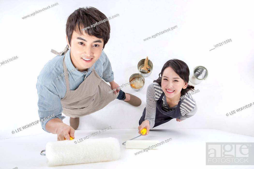 Imagen: Young smiling couple painting.