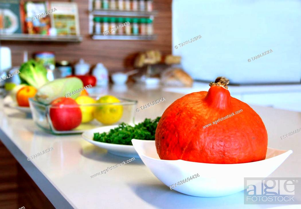 Stock Photo: Well designed modern kitchen with a big variation of ripe fruit and vegetables on the table.