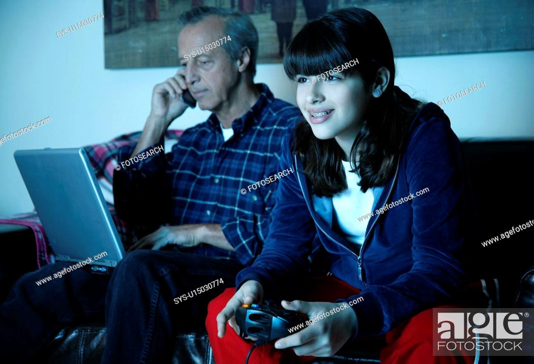 Stock Photo: Grandfather works on laptop while granddaughter plays video game.