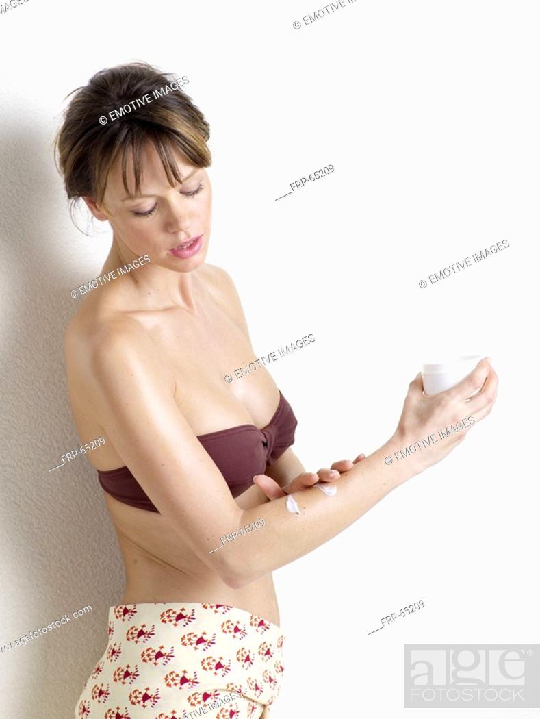 Stock Photo: Woman applying body lotion.