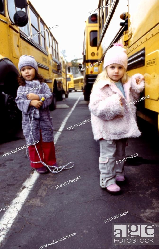 Stock Photo: Two young girl poses in front of a school bus.