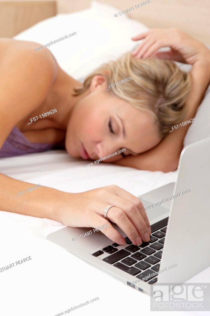 Stock Photo: Young woman fallen asleep while on her laptop.