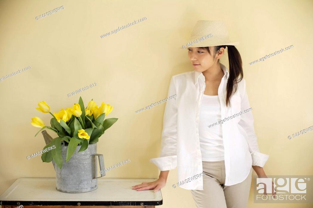 Stock Photo: View of a young woman looking at watering can.