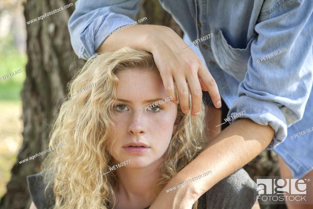 Stock Photo: Blonde teenage girl outdoors, with hands from another teenage girl resting on her.