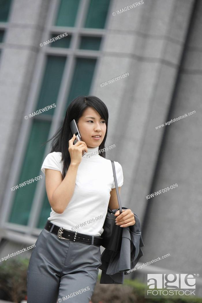 Stock Photo: A woman moves on while conversing on the mobile phone.