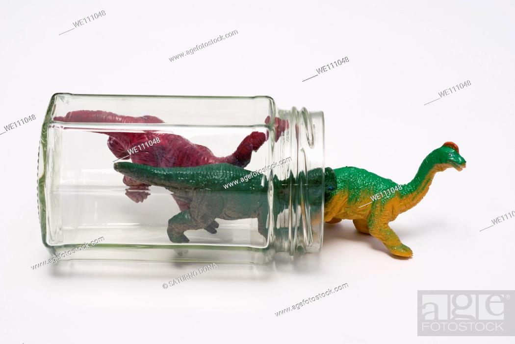 Stock Photo: plastic dinosaurs getting out of glass jar.
