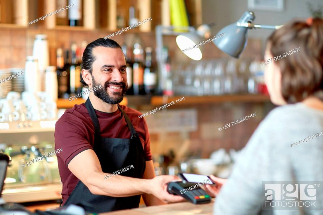 Stock Photo: small business, people and service concept - happy man or waiter in apron with card reader and customer with smartphone paying at bar of coffee shop.