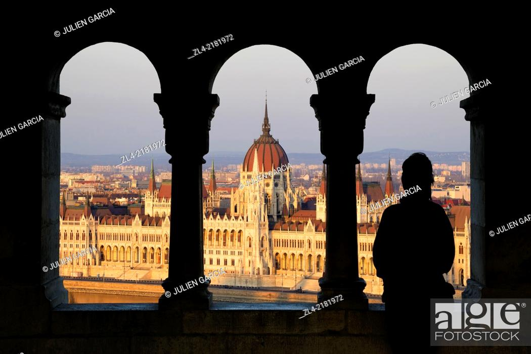 Stock Photo: Silhouette of a woman watching the Hungarian Parliament Building from the Fisherman's Bastion at sunset. Hungary, Budapest. Model Released.