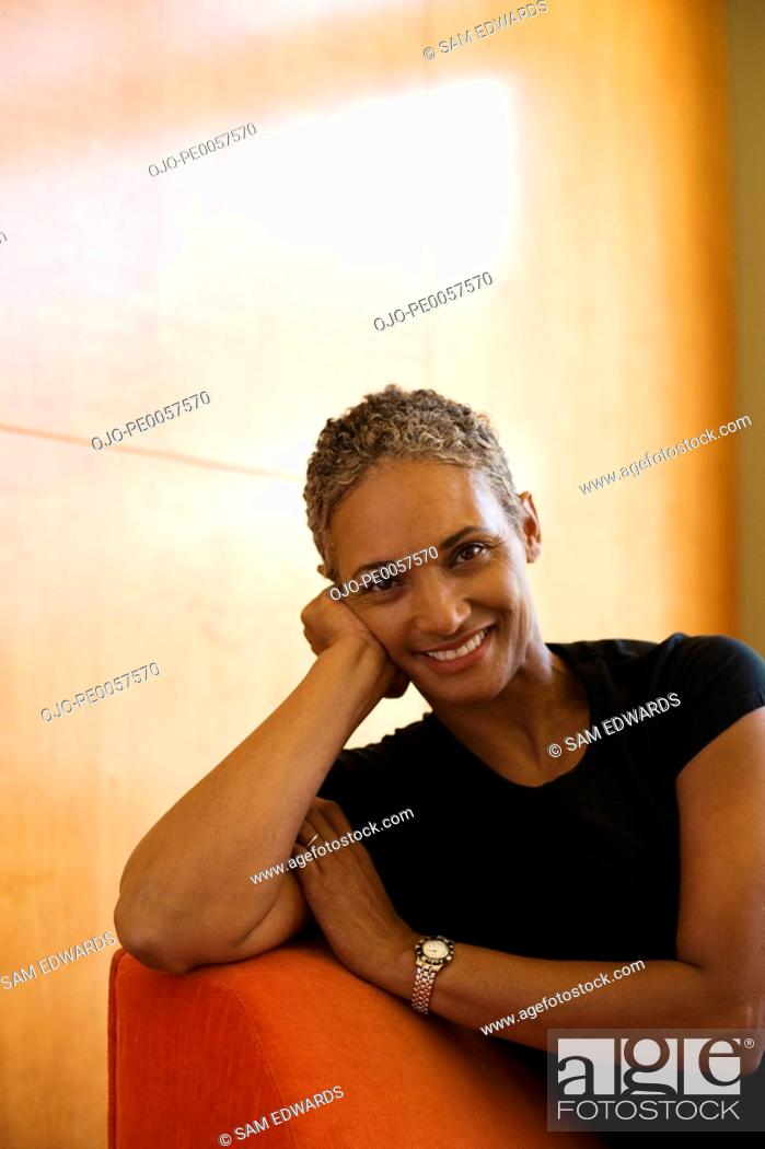 Stock Photo: Woman sitting on sofa in modern home relaxing.