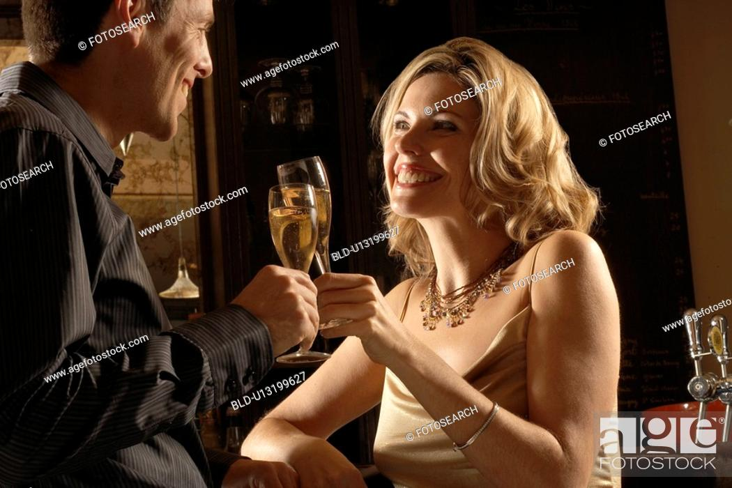Stock Photo: Mid adult couple toasting with champagne.