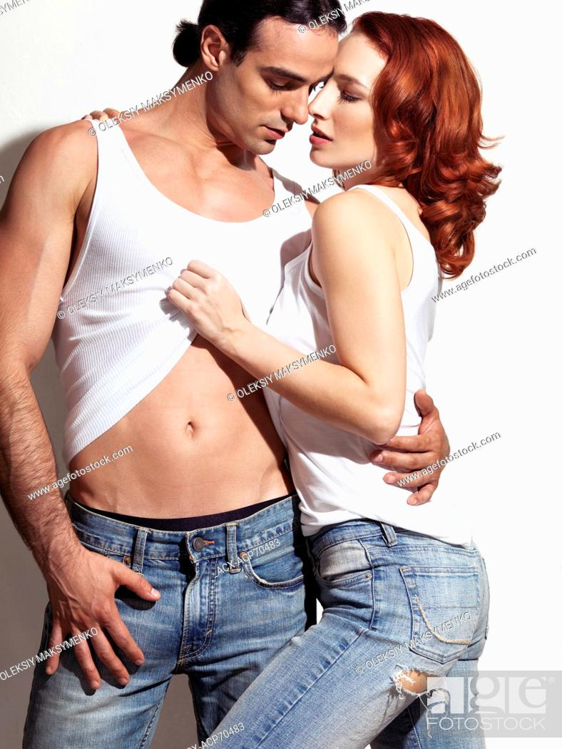 Stock Photo: Sensual portrait of a sexy young couple in blue jeans and white tank tops on white background.