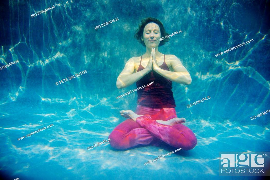 Stock Photo: Mature woman wearing red yoga pants and vest, in yoga position, underwater view.