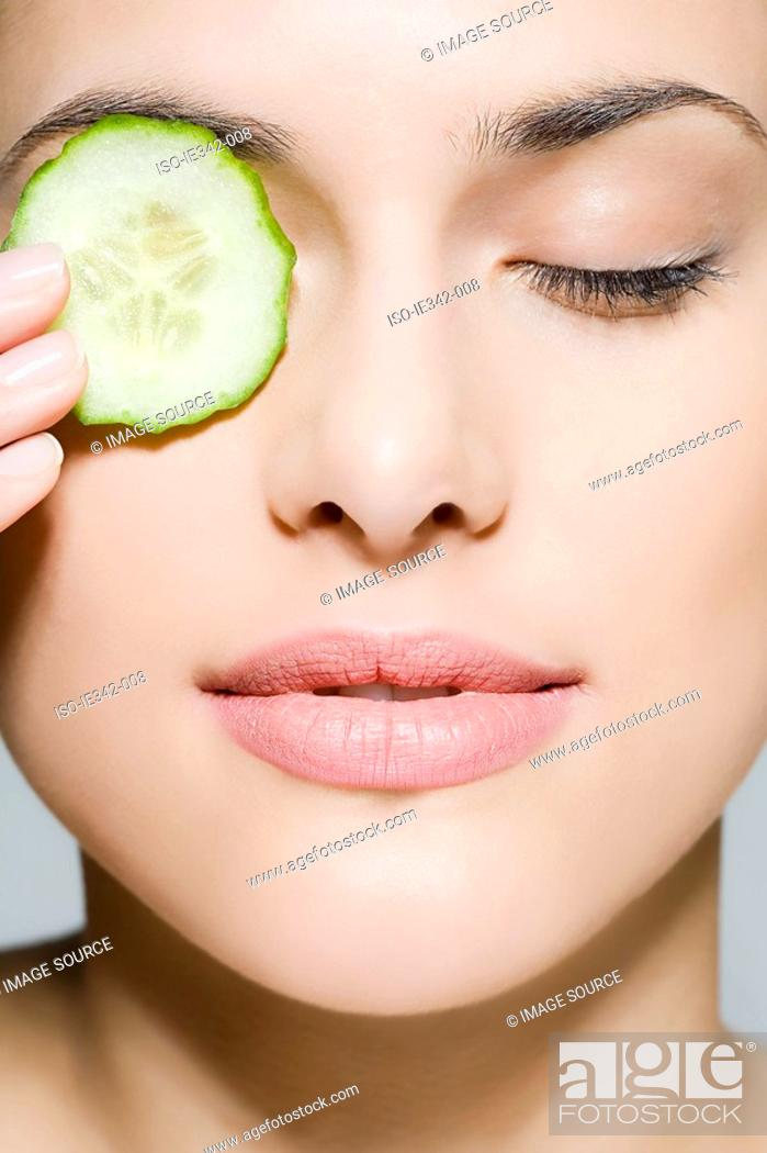 Stock Photo: Woman with cucumber over her eye.