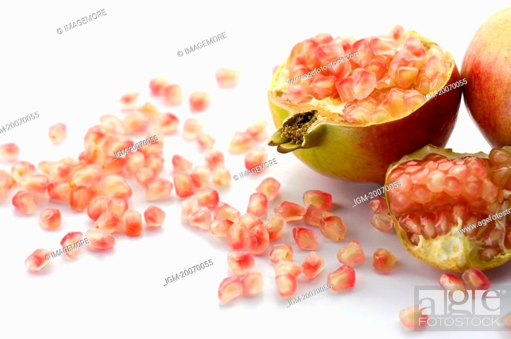 Stock Photo: Pomegranate and scattered seeds.