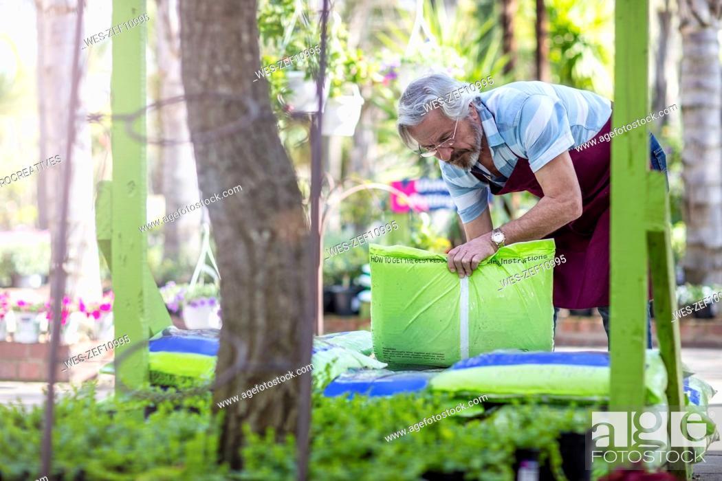 Stock Photo: Elderly gardener stacking bags in garden centre.