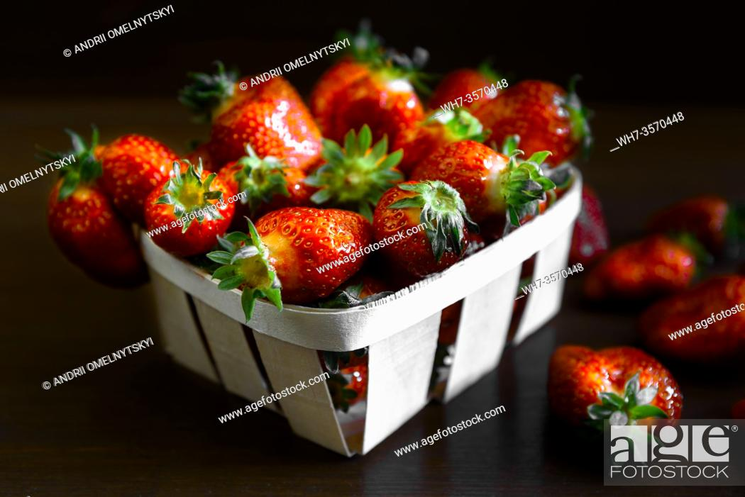 Stock Photo: ripe juicy strawberries on a wooden table in a basket.