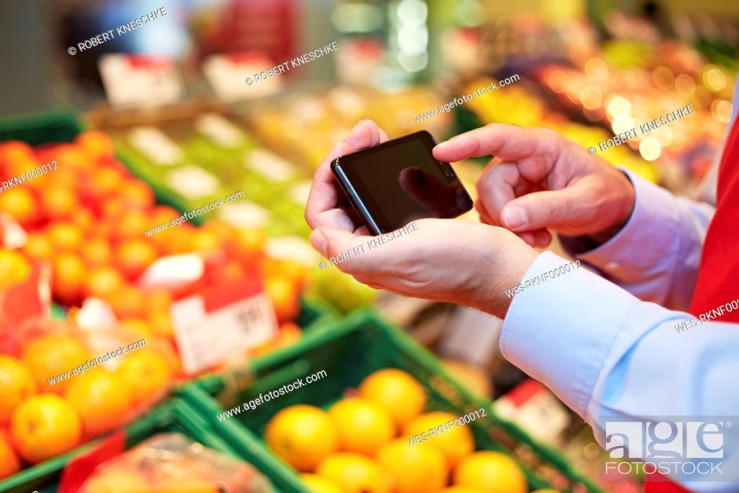 Stock Photo: Germany, Cologne, Mature man using smart phone in supermarket.