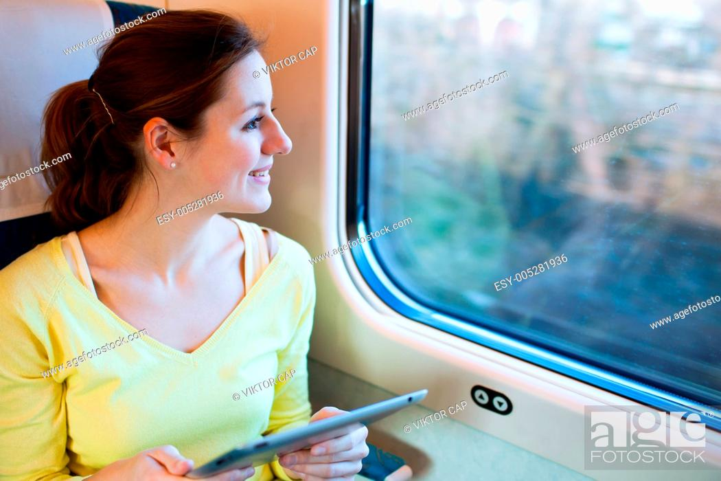 Stock Photo: Young woman using her tablet computer while traveling by train.