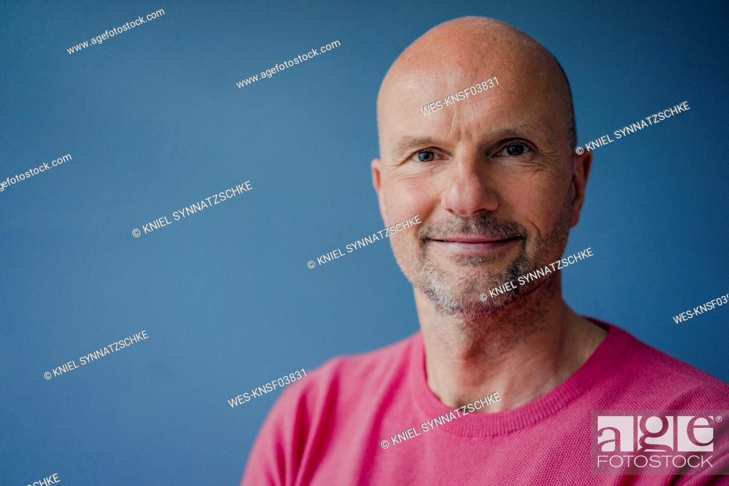 Imagen: Portrait of smiling mature man wearing pink pullover.