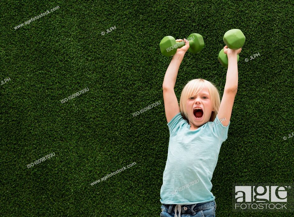 Stock Photo: Boy in front of artificial grass lifting dumbbells.