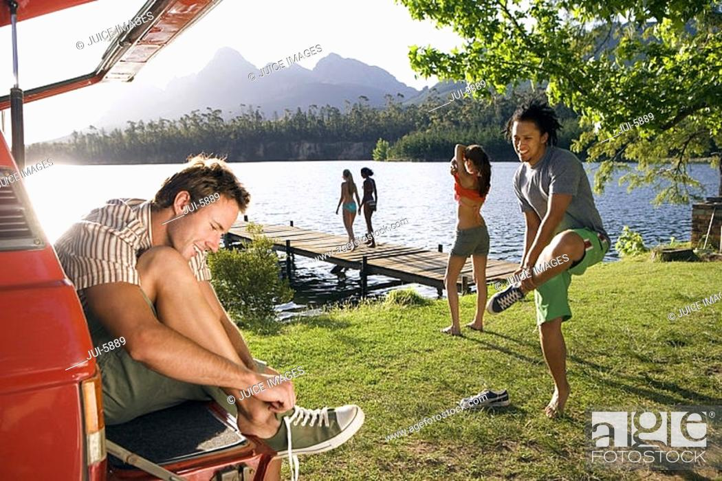 Stock Photo: Group of young adults undressing at the side of lake, two women on jetty, man sitting in boot of car.