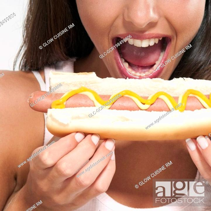 Stock Photo: Close-up of a woman eating a hot dog.