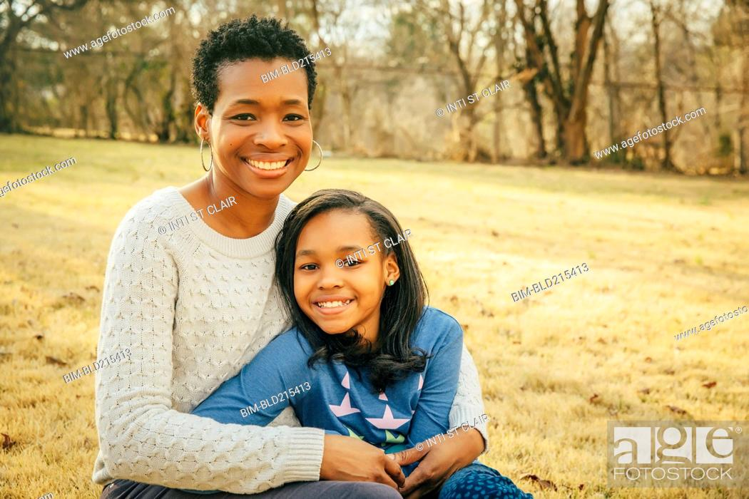 Stock Photo: Black mother and daughter sitting outdoors.