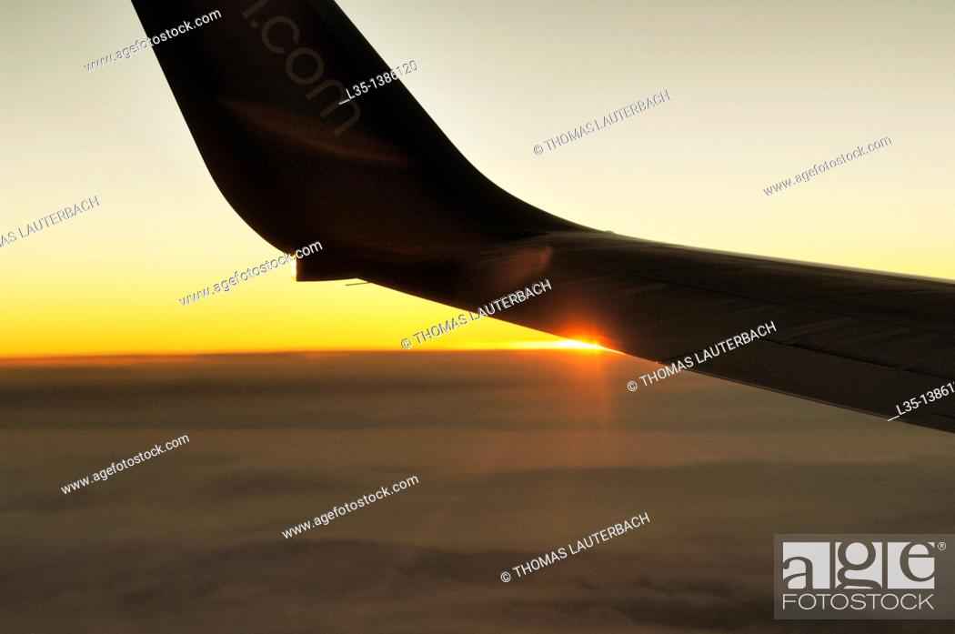 Stock Photo: Position light of an aircraft in flight above the clouds at sunset.