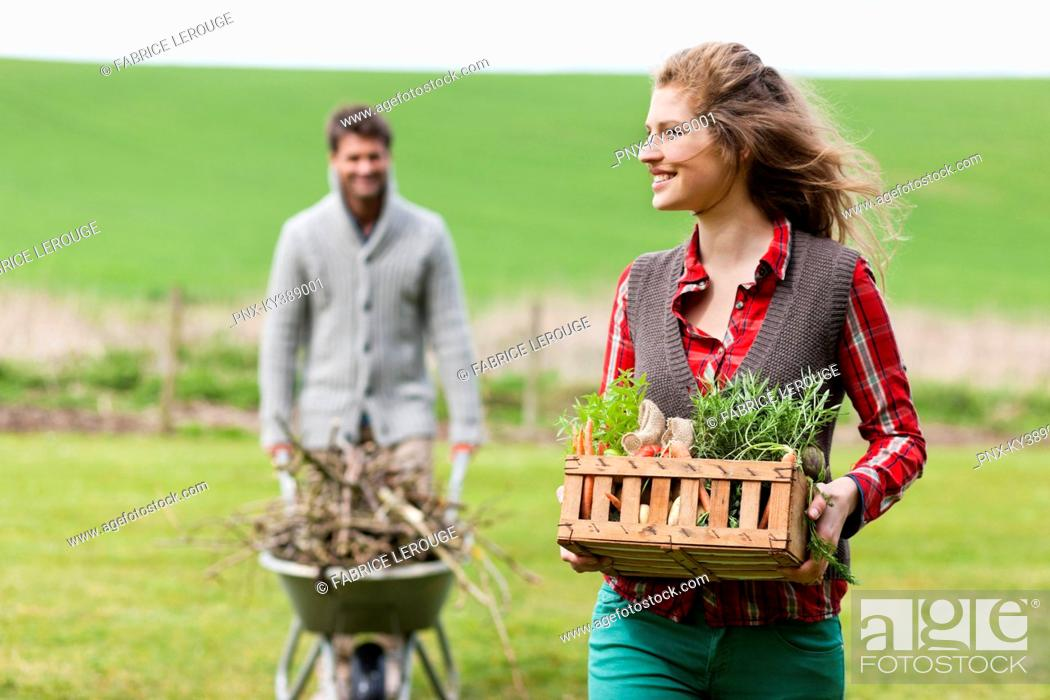 Stock Photo: Woman holding a basket of vegetables with her husband collecting firewood.