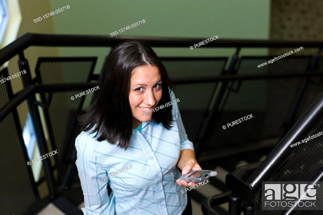 Stock Photo: Portrait of a businesswoman standing on stairs holding a mobile phone.