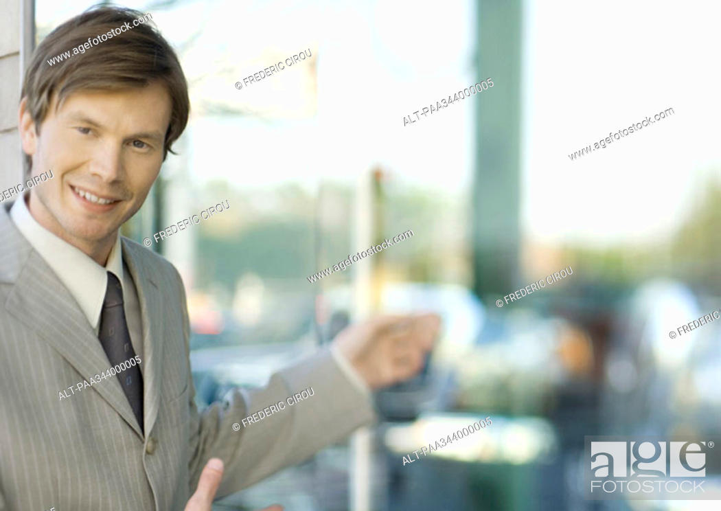 Stock Photo: Young businessman smiling at camera and gesturing.