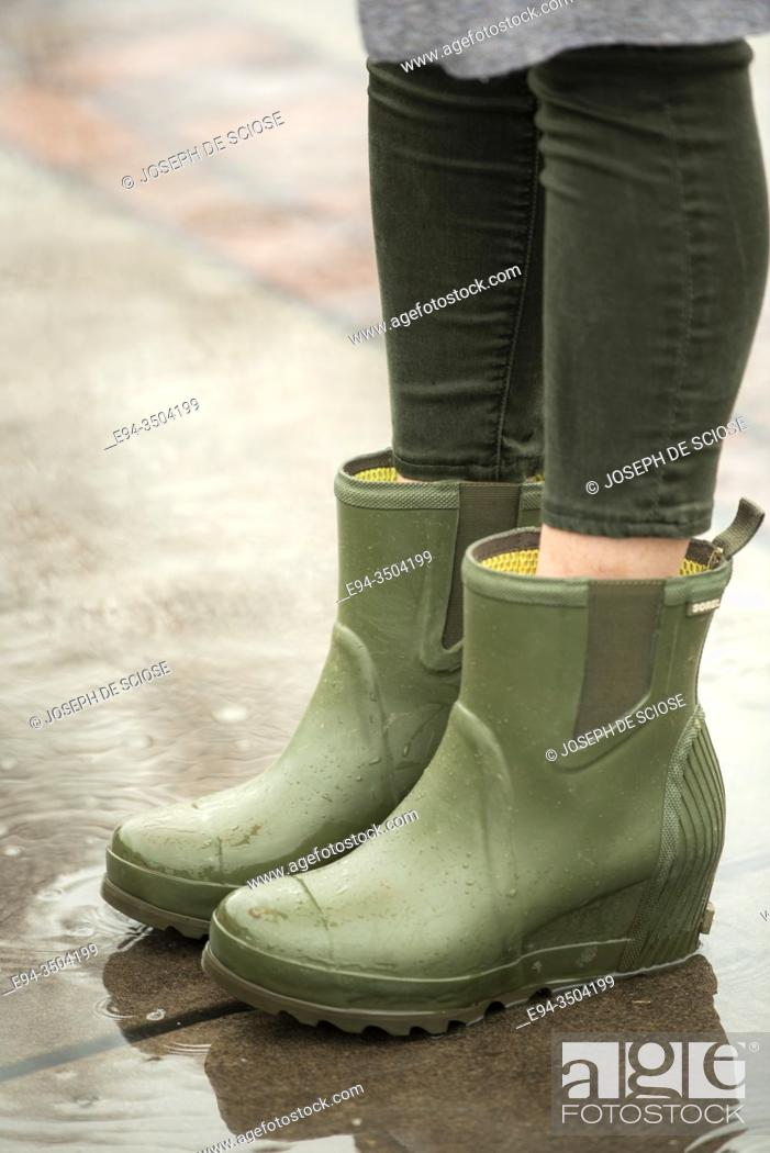 Stock Photo: A woman's feet wearing rubber rain boots splashing in a puddle.