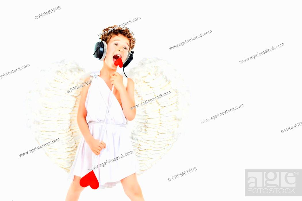 Stock Photo: Cheerful little boy in a costume of angel listening to music in headphones and singing. Cupid. Valentine's day.