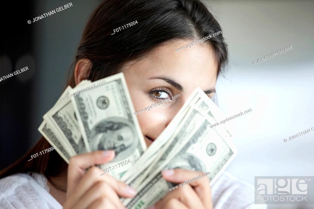 Stock Photo: Woman peeking behind hundred dollar bills.