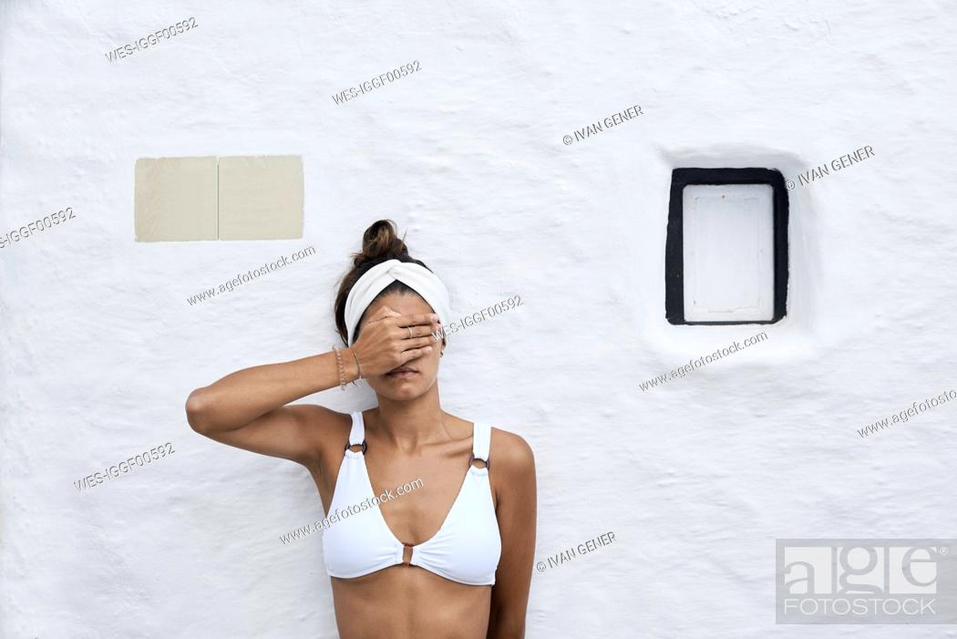 Stock Photo: Young woman wearing white bikini top leaning against white wall covering eyes with her hand.