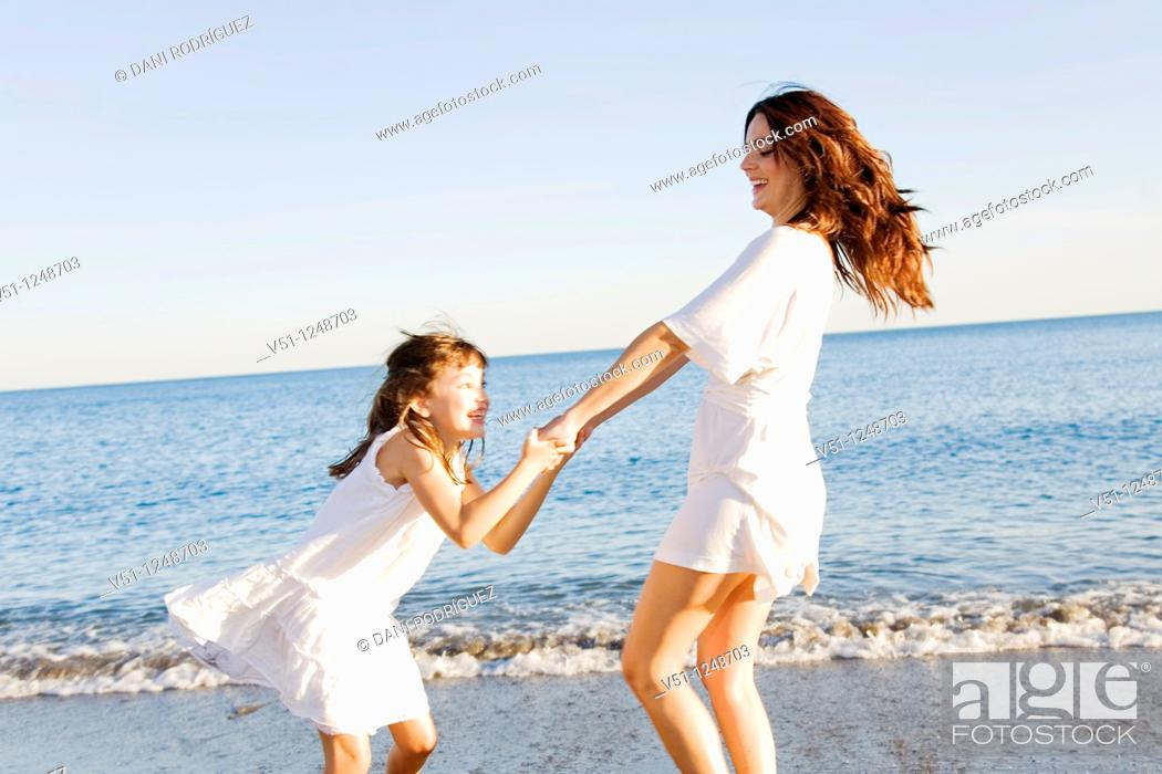 Stock Photo: Mother and daughter having fun in the beach.