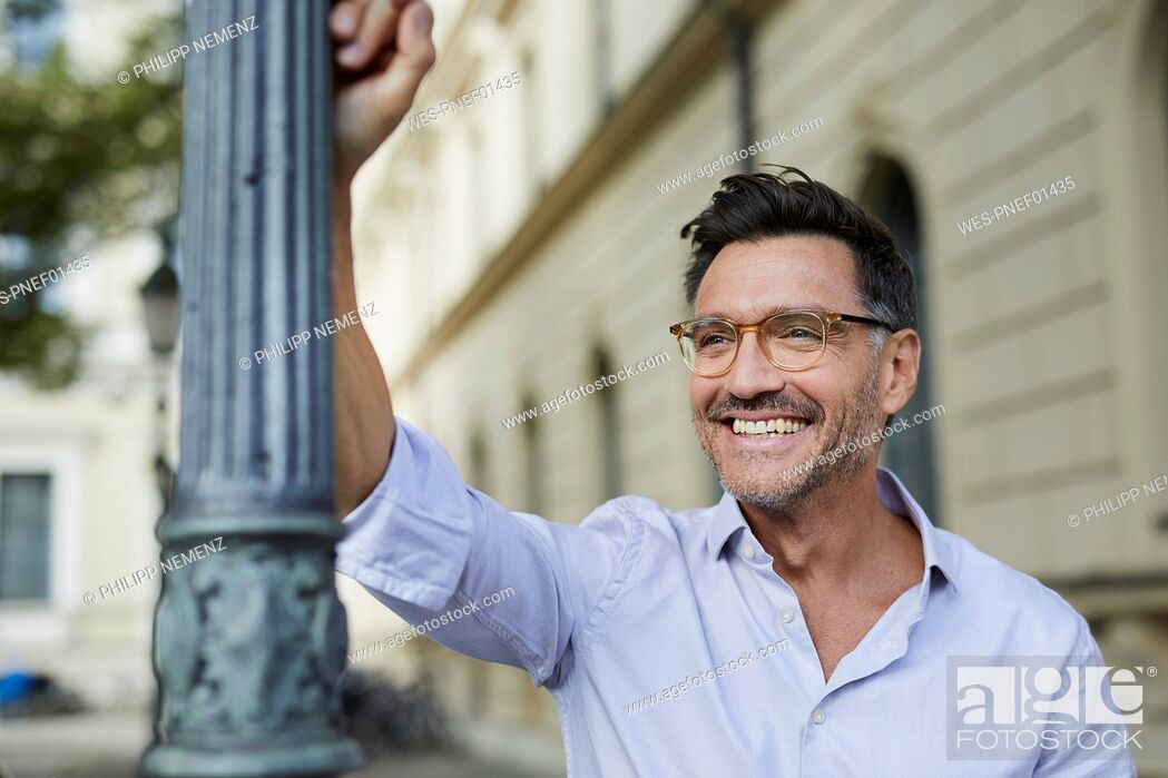 Stock Photo: Portrait of happy businessman leaning against lamp post in the city.