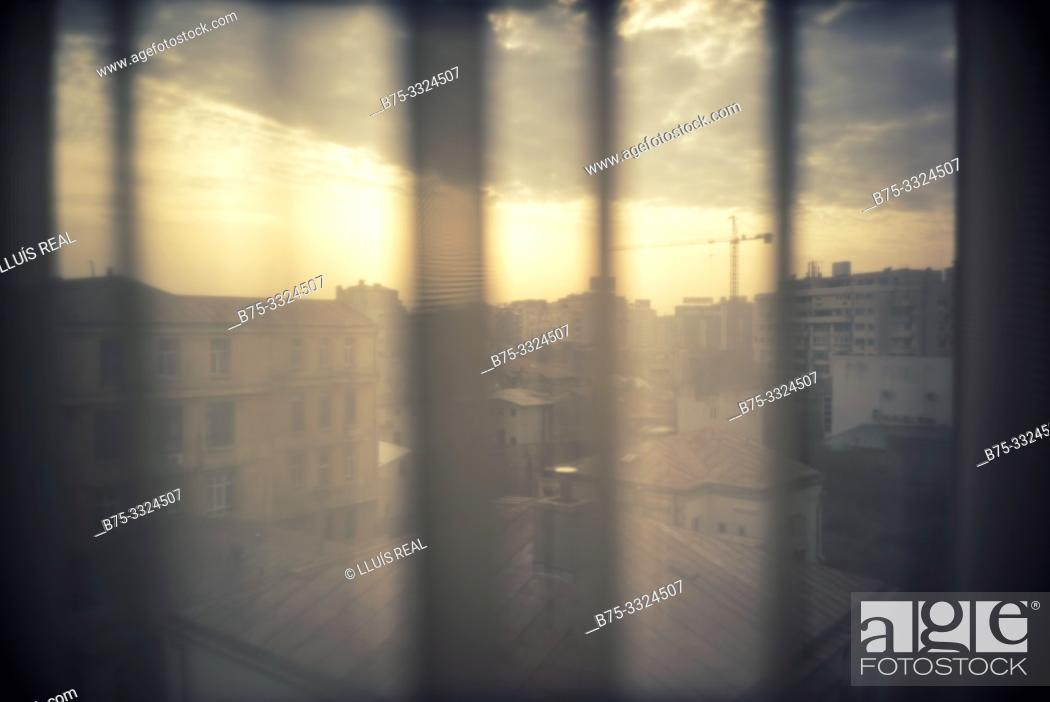 Stock Photo: View across a window with a curtain at the dawn of the city. Bucharest, Romania, Europe.