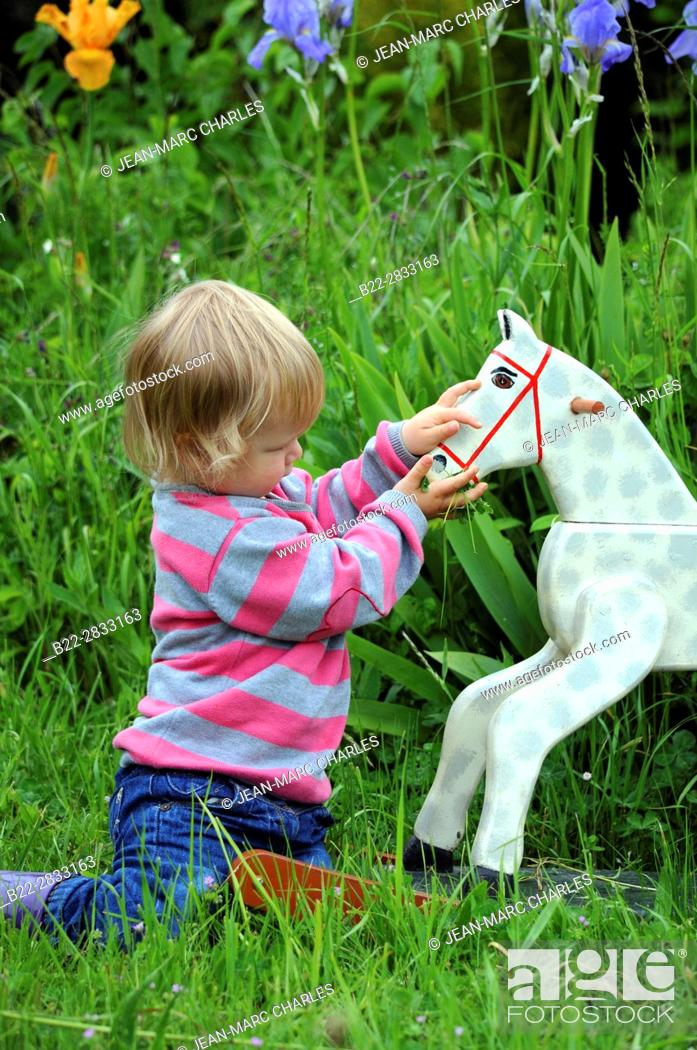 Stock Photo: 2 years old girl playing with a wooden horse.