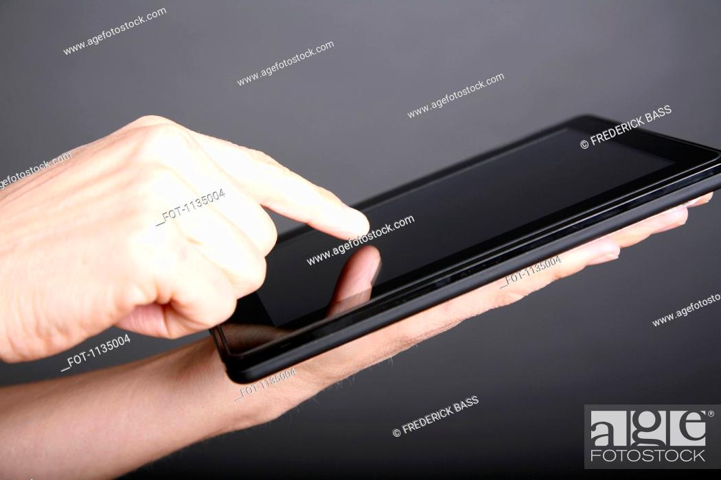 Stock Photo: A man using a digital tablet, close-up of hand.