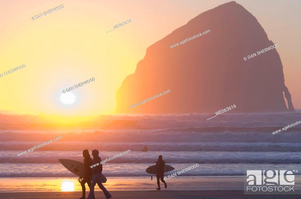 Stock Photo: Silhouetted Surfers at Sunset - Pacific City, Oregon, USA.