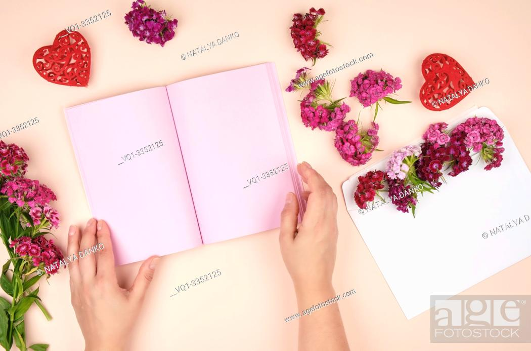 Photo de stock: two female hands and an open notebook with pink blank sheets, next to a bouquet of flowers, top view, pastel background.