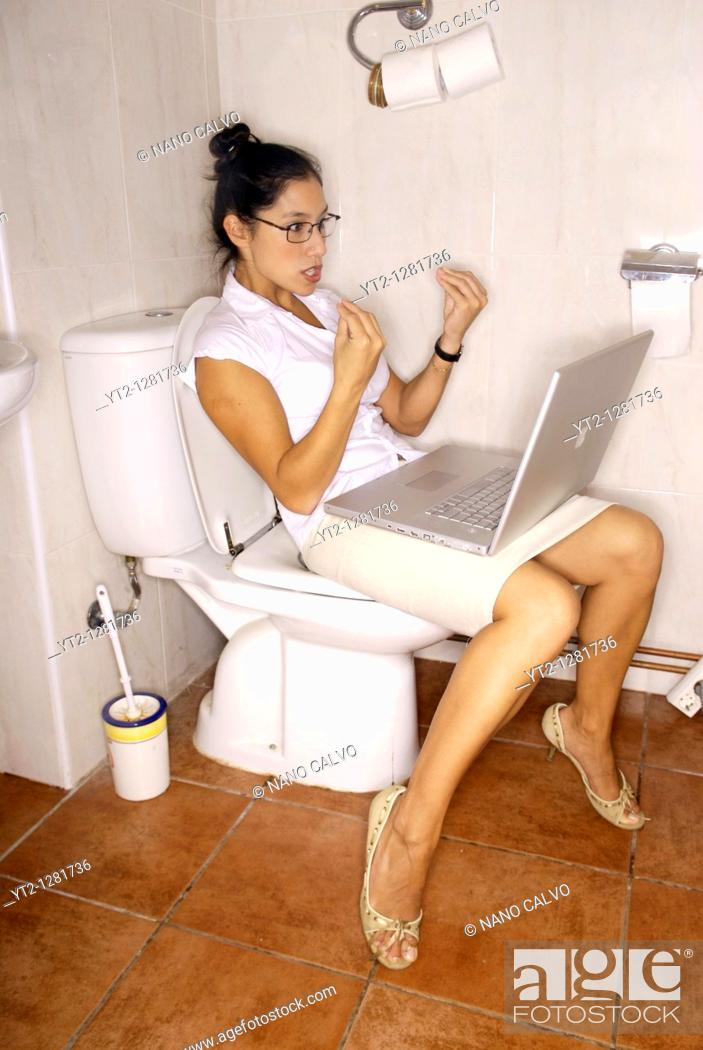 Stock Photo: Comical image of an executive young woman working in the bathroom in a rush.