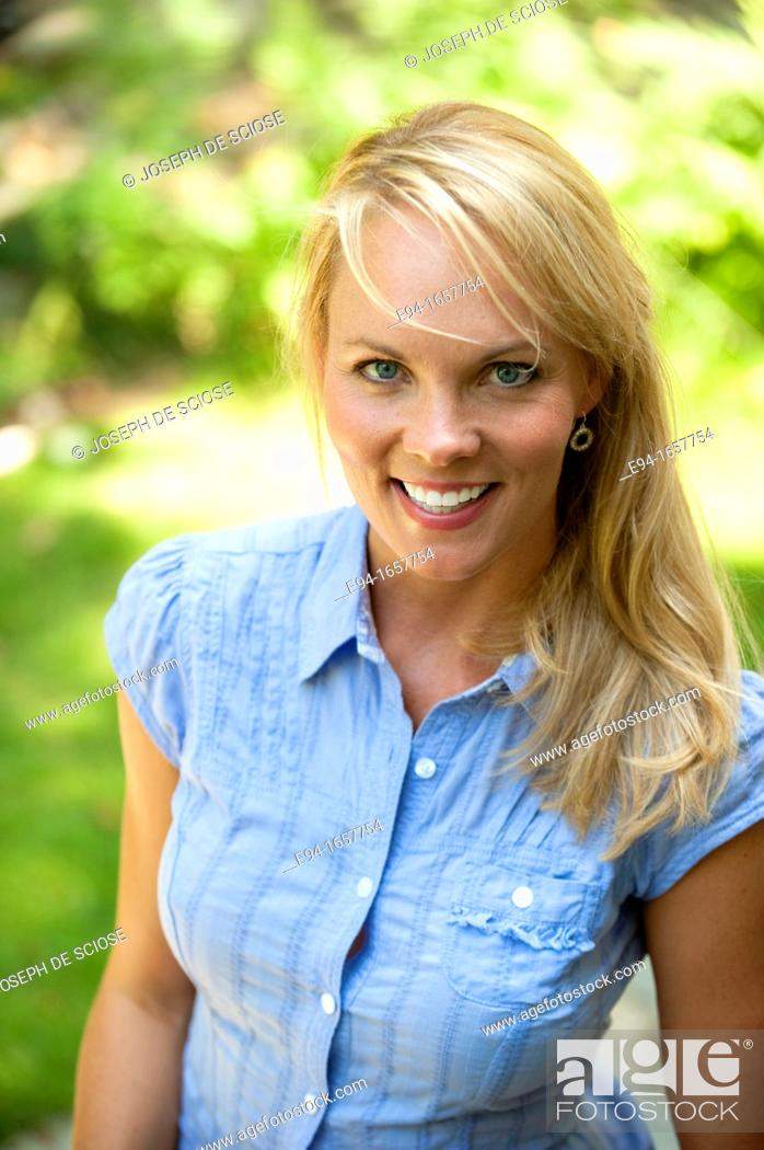 Stock Photo: Portrait of a 35 year old blond woman wearing a blue blouse and jeans in a garden setting looking at the camera.