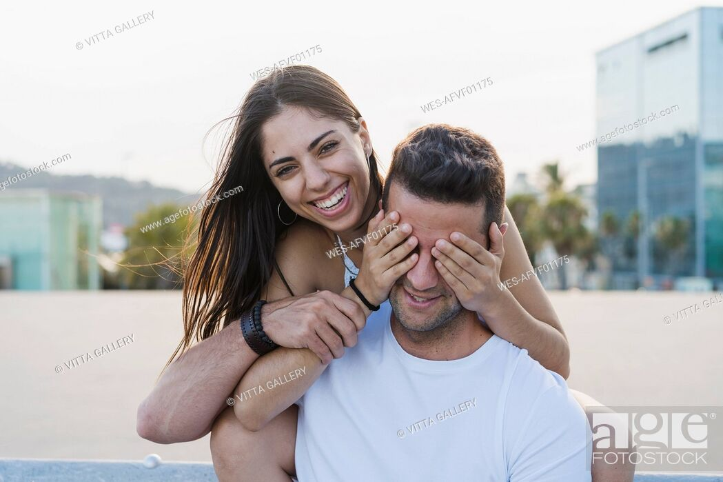 Stock Photo: Laughing young woman surprising her boyfriend, covering his eyes.