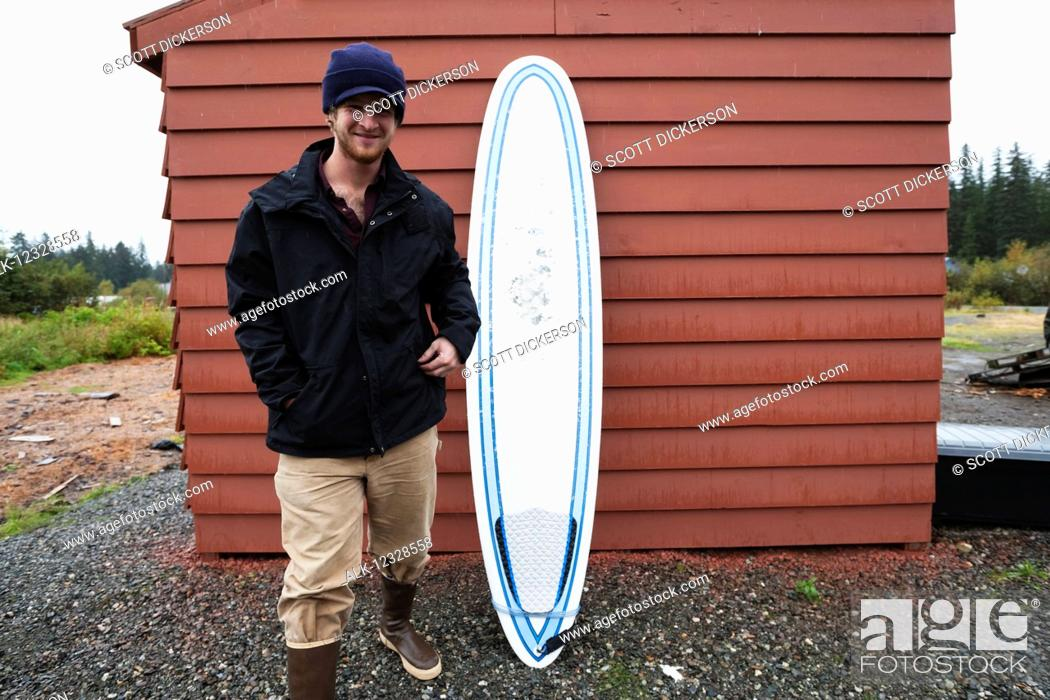 Photo de stock: Young man standing next to a surfboard, South-central Alaska; Homer, Alaska, United States of America.