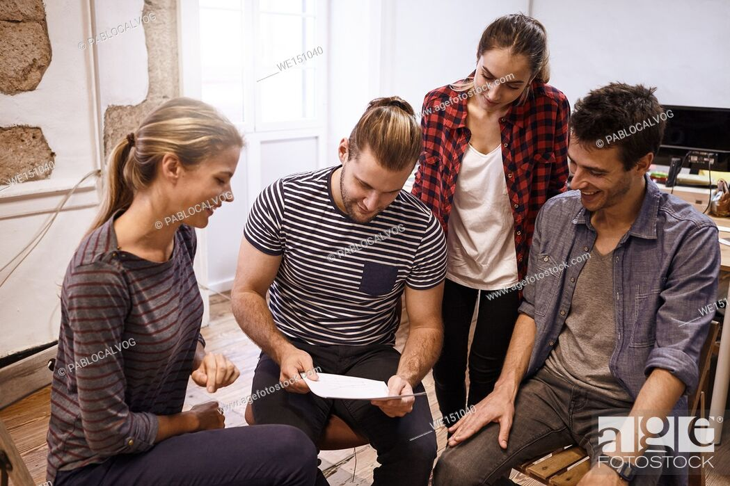 Stock Photo: Young business team sitting and standing around in a semi circle all looking thoughtfully at memorandum while one is leading the team.