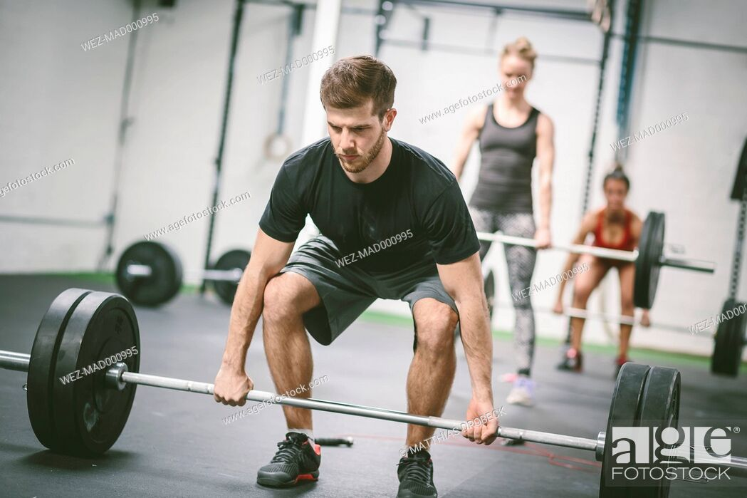 Stock Photo: People in gym lifting weights.