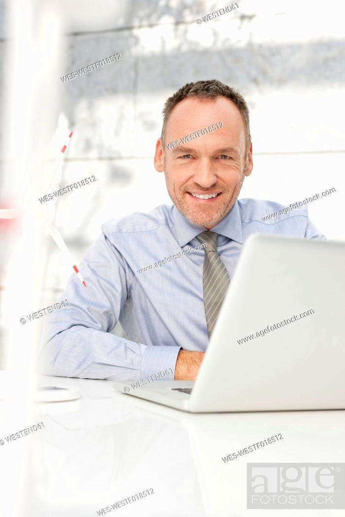 Stock Photo: Germany, Leipzig, Businessman using laptop with wind power model.