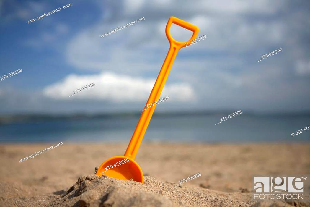 Stock Photo: childs toy plastic spade stuck into the sand on a beach in the uk.